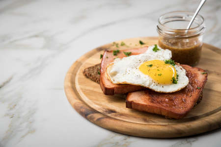Roasted Bavarian Leberkaese meat loaf with fried egg on sunflower seed bread with sweet mustard on wooden board Reklamní fotografie