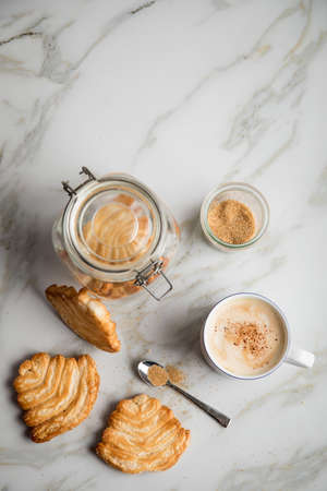 Italian puff pastry fan wavers cookies biscuits with preserving glass jar and cup of coffee on marble table background