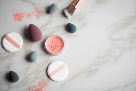 Loose rouge make-up powder with blender, sponge and brush on marble beauty table Фото со стока