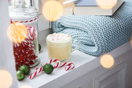 Hot white chocolate with whipped cream and marshmallows on windowsill with cosy wool rug blanket and book at Christmas X-Mas Advent weekend with light bokeh