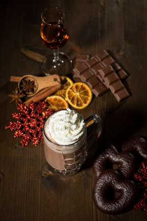 Hot dark Russian chocolate during holiday season with whipped cream, amaretto spiced rum, spices, Lebkuchen, red glitter snowflake Christmas ornaments on dark wooden background Stock fotó