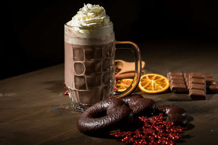 Hot dark chocolate during holiday season with whipped cream, spices, Lebkuchen, red glitter snowflake Christmas ornaments on dark wooden background Stock fotó