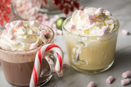 Hot dark chocolate during holiday season with whipped cream, marshmallows, candy canes, Christmas tree ornaments, green glitter balls and red snowflake on light marble background