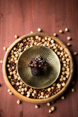 Hazelnut muffin in golden metal bowl on nuts and wooden table background