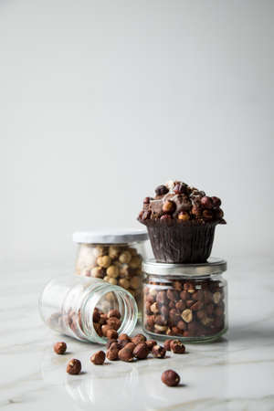 Hazelnut muffin with  walnuts and hazelnuts in jars on light marble table background