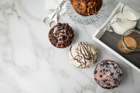 Muffin selection with blueberry, walnuts, hazelnuts and white chocolate with milk and sugar for coffee break on marble table and green background
