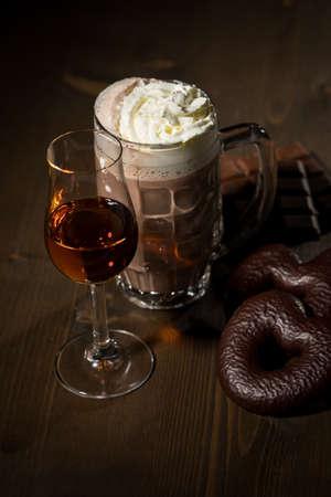 Hot dark Russian chocolate with whipped cream, amaretto spiced rum and German Lebkuchen on dark wooden background
