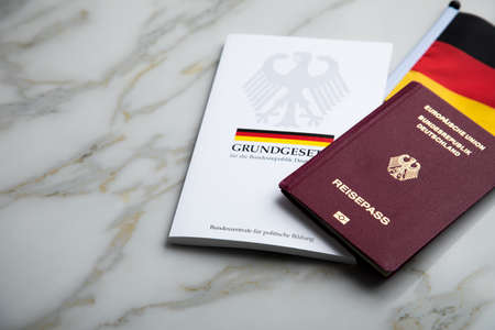 Passport and  constitution basic law book of Germany with flag on marble background Редакционное