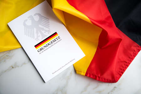 The book of German constitution basic law on flag of federal republic of Germany and marble background Редакционное