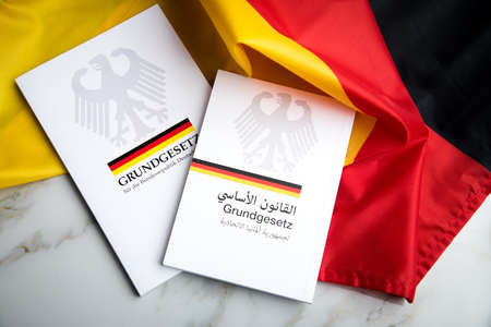The constitution basic law book of Germany in German and Arabic language on flag and marble background Редакционное
