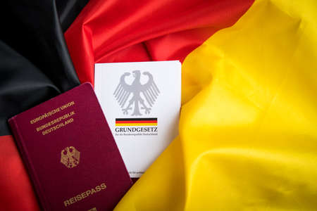 Passport and  constitution basic law book of Germany on German flag