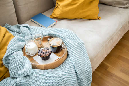 Blueberry muffin with coffee, sugar and milk on wooden tray and comfy sofa with blue wool knit blanket, yellow cushions and book