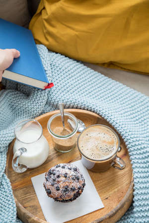 Woman reading book and having blueberry muffin with coffee, sugar and milk on wooden tray and comfy sofa with blue wool knit blanket, yellow cushions and book Stock fotó