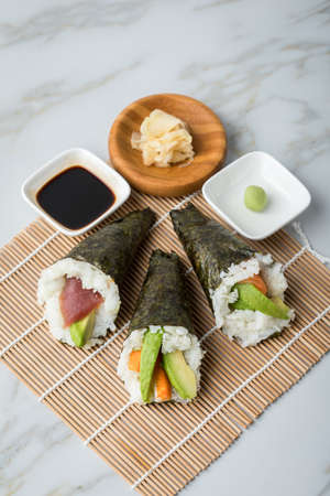 Salmon, tuna fish and Surimi avocado Temaki sushi with soy sauce, pickled ginger and wasabi on mat and marble background Фото со стока