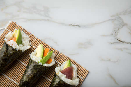 Salmon, tuna fish and Surimi avocado Temaki sushi in row on mat and marble background Фото со стока - 138644107