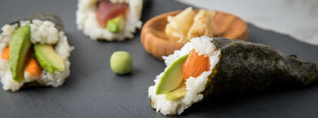 Salmon, tuna fish and Surimi avocado Temaki sushi with pickled ginger and wasabi on slate plate and marble background