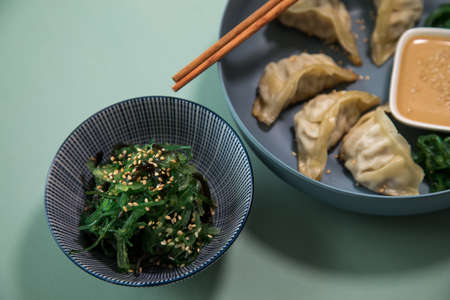 Fried Dim Sum Gyoza dumplings with Wakame seaweed salad and sesame sauce in bowl with wooden chopsticks for lunch Фото со стока