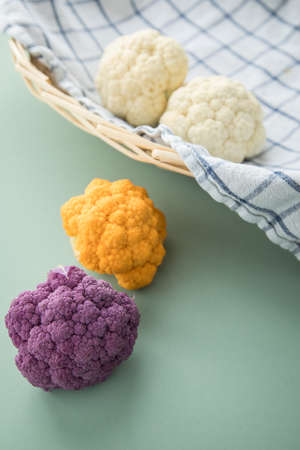 Colorful rainbow cauliflower in purple, orange and white on kitchen towel with knife in basket on pastel mint green background