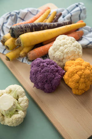 Colorful rainbow cauliflower and carrots veggies in purple, white, orange and yellow with wooden board and kitchen towel on pastel green background
