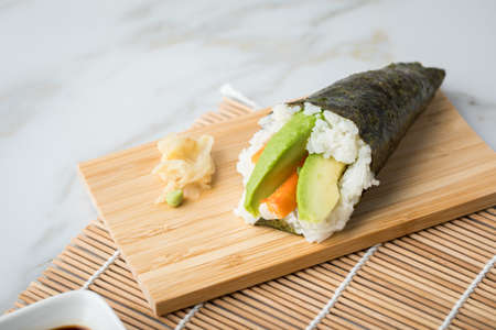 Surimi avocado Temaki sushi with soy sauce, pickled ginger and wasabi on mat, bamboo tray board and marble background