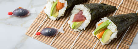Salmon, tuna and Surimi avocado Temaki sushi with soy sauce fish, pickled ginger and wasabi on mat and marble background Фото со стока