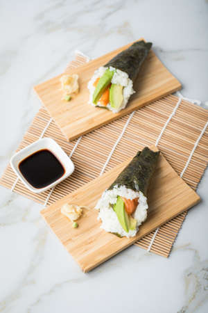 Salmon fish and Surimi avocado Temaki sushi with soy sauce, pickled ginger and wasabi on mat, bamboo tray board and marble background