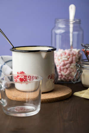 Preparation and cooking of hot white chocolate in milk pot with instant powder and marshmallows in domestic kitchen on dark wooden counter top and lilac background