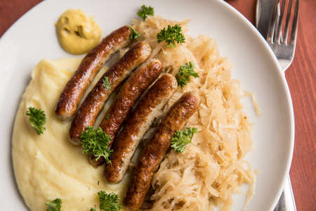 Small fried Bavarian German Nürnberger sausages with sauerkraut, mashed potatoes and mustard on wooden table background Фото со стока