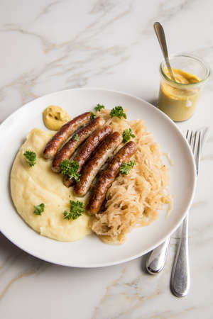 Small fried Bavarian German Nürnberger sausages with sauerkraut, mashed potatoes and mustard on marble table background
