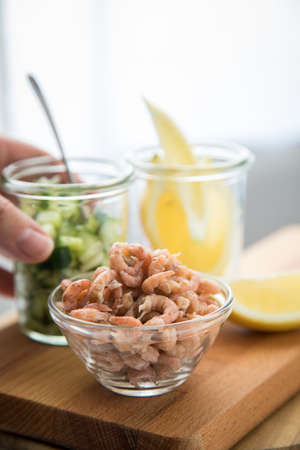 Woman eating German Friesland north sea brown shrimps in glass bowl with cucumber salad and lemon of wooden board