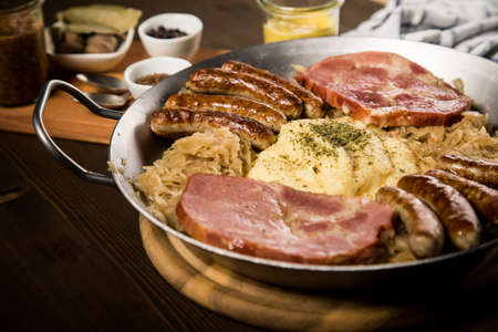 Sauerkraut pan with small fried Bavarian German Nürnberger sausages, smoked Kassler pork neck, mashed potatoes, mustard and spice ingredients on wooden table Фото со стока - 138962662