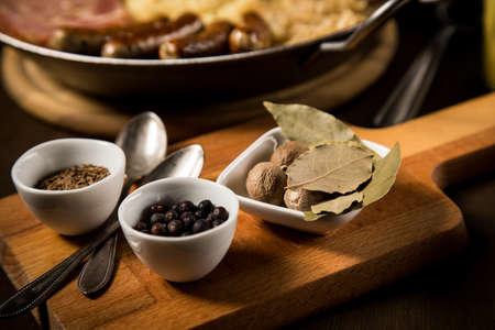 Sauerkraut spices bay, leaf, juniper, berries, caraway, seeds, nutmeg, with kraut pan, fried German Nürnberger sausages, Kassler pork neck, mashed potatoes, mustard on wooden table Фото со стока - 138962200
