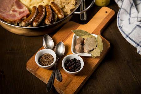 Sauerkraut spices bay, leaf, juniper, berries, caraway, seeds, nutmeg, with kraut pan, fried German Nürnberger sausages, Kassler pork neck, mashed potatoes, mustard on wooden table Фото со стока - 138962293