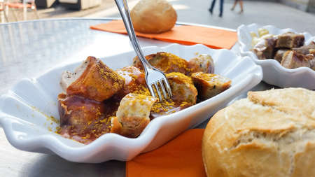 Currywurst a typical German street food grilled and sliced sausage with curry ketchup and bread roll bun Stock Photo