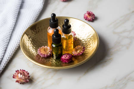 Tree bottles of natural organic beauty face oil serum for cosmetic anti age treatment skin care with towel, gold metal bowl, dried flowers and marble background