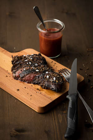 Beef sirloin steak on cutting board with ketchup, salt and pepper on dark wooden background