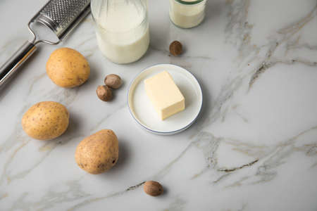 Potato, milk, salt, butter, nutmeg as ingredients with press and grinder for mashed potatoes on light marble background