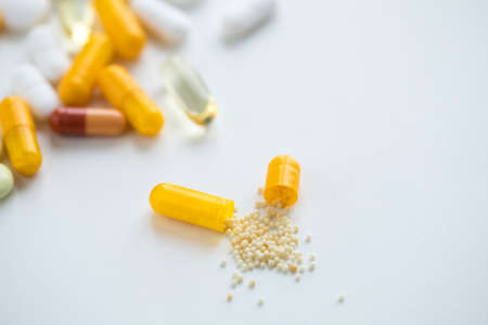 White and yellow pills, tablets and capsule medicine on white background