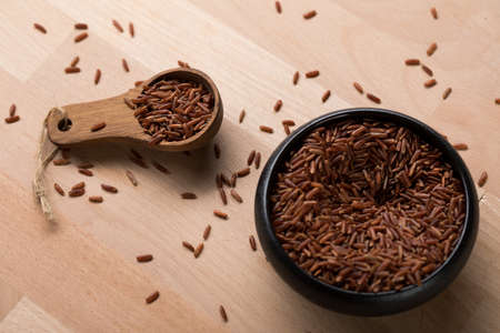 Red skinned raw Jasmine rice in black bowl with spoon on wooden background and is a specialty from Cambodia Asia