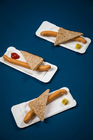 Three Wiener sausages with whole grain bread slice on disposable paper plate with mustard and ketchup on blue background Фото со стока