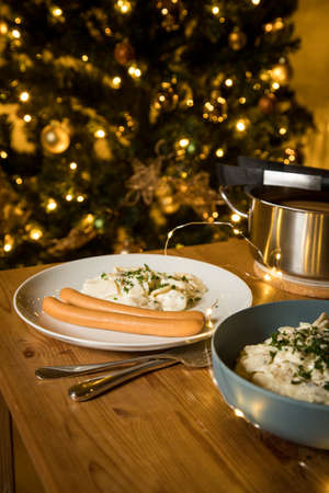 Wiener sausages and potato salad as typical German Christmas eve holiday dinner with decorated Christmas tree and fairy lights on wooden table Фото со стока