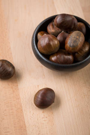 Sweet chestnuts in black bowl on wooden background