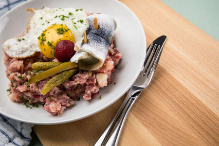 North German Hamburg Labskaus is a delicacy with corned beef, potatoes, beetroot, pickled gherkins, fried egg and herring on porcelain plate