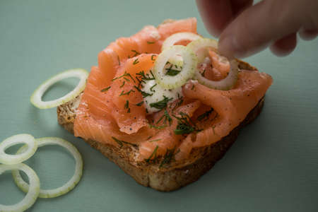Woman eating smoked salmon on whole grain toast with onion rings, dill and horseradish of wooden board