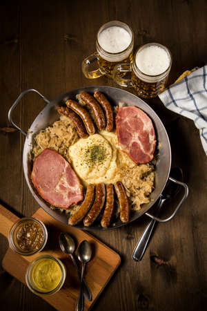 Sauerkraut pan with small fried Bavarian German Nürnberger sausages, smoked Kassler pork neck, mashed potatoes, mustard and beer on wooden table