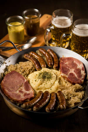 Sauerkraut pan with small fried Bavarian German Nürnberger sausages, smoked Kassler pork neck, mashed potatoes, mustard and beer on wooden table Фото со стока