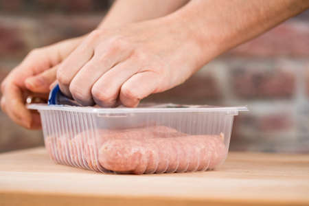 Woman with raw fresh coarse sausages with pork meat in plastic tray packaging