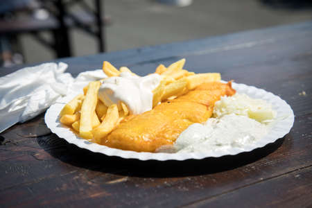 Typical German Friesland deep fried Pollack fish in beer batter with French fries, mayonnaise, sauce tartar and coleslaw on wooden table