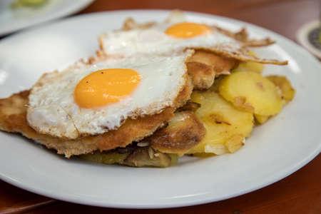 Pork meat Schnitzel Hamburg style with fried eggs and roast potatoes in Biergarten restaurant