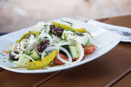 Greek farmer salad with olives, pepper, cucumber, feta cheese, tomatoes and onions on wooden table
